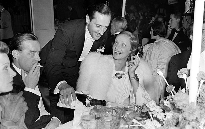 LOS ANGELES,CA - CIRCA 1940: Actress Marlene Dietrich smiles at actor Basil Rathbone as he pours her a drink during an event in Los Angeles, California. (Photo by William Grimes/Michael Ochs Archives/Getty Images)