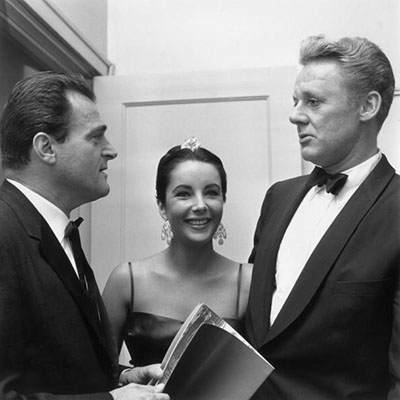 October 1957: EXCLUSIVE British-born actor Elizabeth Taylor stands between her third husband, American producer Mike Todd (L), and American actor Van Johnson at an event for director Edward Dmytryk's film, 'Raintree County,' in which Taylor starred, Los Angeles, California. Taylor is wearing a spaghetti-strap gown and has her hair slicked back, and the men are in tuxedos. (Photo by M. Garrett/Murray Garrett/Getty Images)