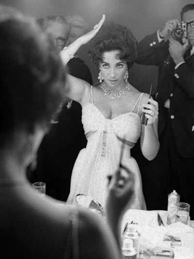 Actress Elizabeth Taylor adjusts her hair in front of the mirror, while photographer John Bryson takes a portrait in the background, 1959. (Photo by John Bryson/The LIFE Images Collection/Getty Images)