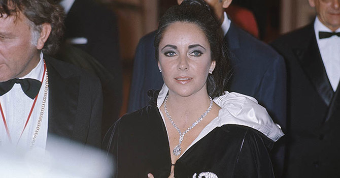 The 40Th Anniversary Of Princess Grace Of Monaco. Bal des Scorpions donn? ? l'h?tel Hermitage de MONACO pour f?ter le 40?me anniversaire de la princesse GRACE : Elizabeth TAYLOR souriante portant autour du cou le diamant de 69,42 carats taill? en forme de poire achet? pour la somme d'un million de dollars par son mari Richard BURTON ? ses c?t?s. (Photo by Jack Garofalo/Paris Match via Getty Images)