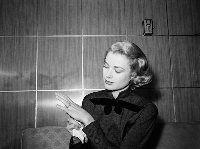 Grace Kelly showing the ruby and diamond eternity band Prince Rainier proposed with to photographers at her parents home in Philadelphia. Photo Getty