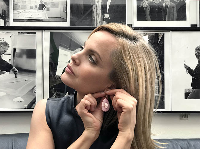 Mena Suvari putting on a pink opal earring by Suzanne Felsen in Sydney Felsen's office at Gemini G.E.L. Photo by Sally Davies