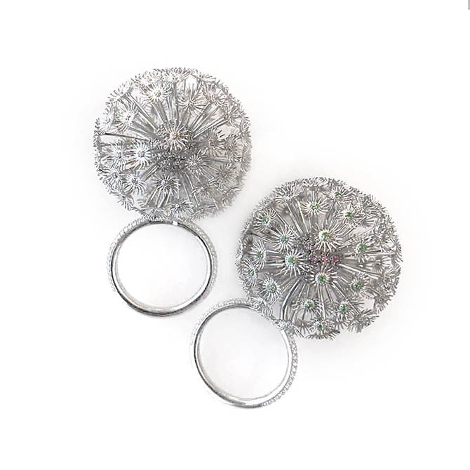 Christian Tse's platinum Dandelion Rings: the design on the left is set with diamonds and the one on the right has pink sapphires on the core and emeralds in the center of the seedlings. Photo by Sally Davies