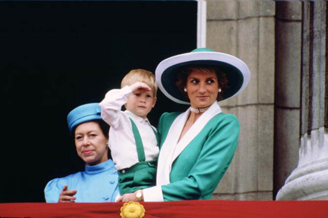 Princess Diana wearing a triple row pearl choker she received as an 18th birthday present from her family. She is holding a young Prince Harry in her arms as she watches Trooping the Colour in June 1988 from the balcony of Buckingham Palace. Princess Margaret is in the background. Photo by Tim Graham/Getty