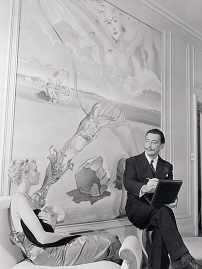 (Original Caption) Salvador Dali sketches model Royal Wittaker wearing his Tree of Life necklace in front of the mural he painted for Helena Rubinstein's New York apartment. One of the artist's most intricate jewelry creations, the Tree of Life consists of a face with star sapphire eyes hanging form an elaborately sculptured virgin gold necklace with diamonds set in the leaves. How much? Only $6,500.