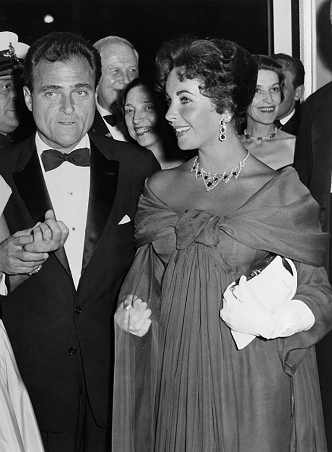 (GERMANY OUT) GB, London. Liz Taylor and her husband Michael Todd visiting the premiere of the movie 'Around the world in 80 days' at the Astoria cinema. She wears a red chiffon evening gown by Dior and diamonds. (Photo by ullstein bild/ullstein bild via Getty Images)