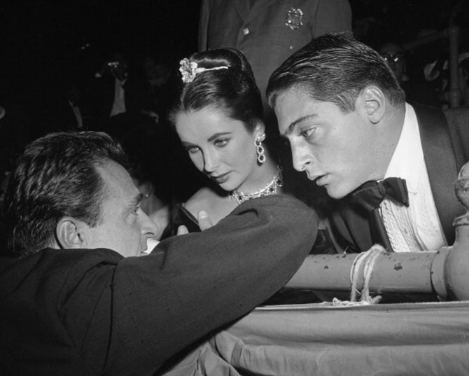 "Michael Todd host private party at Madison Square Garden for ""Around the World in 80 Days"". Mike Todd leans on Garden rail to talk with his wife, Liz Taylor, and his son by an earlier marriage, Mike Jr. (Photo By: Mathewson, Hal/NY Daily News via Getty Images)"