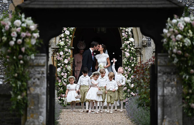 Pippa Middleton (centre R) kisses her new husband James Matthews, following their wedding ceremony at St Mark's Church in Englefield, west of London, on May 20, 2017, as the bridesmaids, including Britain's princess Charlotte (L) and pageboys, including Britain's prince George (2R), walk ahead. After turning heads at her sister Kate's wedding to Prince William, Pippa Middleton graduated from bridesmaid to bride on Saturday at a star-studded wedding in an English country church. The 33-year-old married financier James Matthews, 41, at a ceremony attended by the royal couple and tennis star Roger Federer, wearing a couture dress by British designer Giles Deacon. / AFP PHOTO / POOL / Justin TALLIS (Photo credit should read JUSTIN TALLIS/AFP/Getty Images)