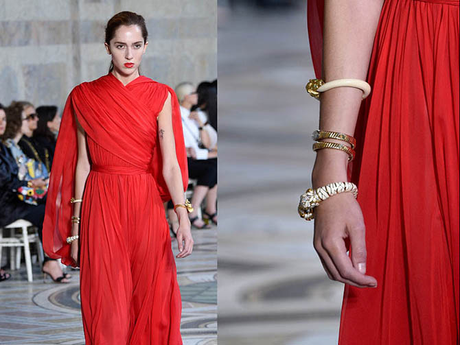 Three vintage bracelets from Eleuteri stacked on the arm of a model in a fire engine red Giambattista Valli dress. The pieces include a gold lion bracelet, a Bulgari tubogas design and a David Webb enamel diamond and ruby jewel. Photo Getty