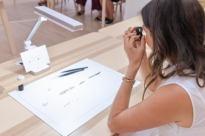 Designer Jade Trau reviewing a rough diamond with a jeweler's loupe in the Forevermark Master Class. Photo by Andrew Werner