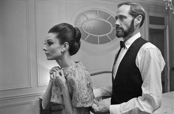 Mel Ferrer with Audrey Hepburn who is wearing one of her wedding bands. The couple is getting ready to attend the 1964 Paris premiere of Hepburn's film 'My Fair Lady.'