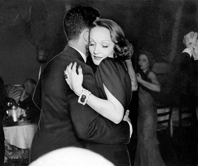 Marlene Dietrich wearing her Trabert & Hoeffer-Mauboussin emerald and diamond bracelet and Flato emerald ring while dancing Cornelius Vanderbilt Whitney at the New York club El Morocco in the 1930s. Photo New York Daily News
