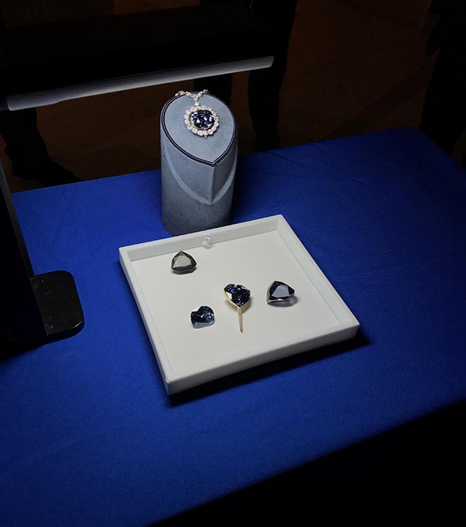 An image take at the press preview on October 20, 2017 of the Hope Diamond on a stand above a tray of the simulations of the lead cast of the French Blue, the Tavernier Blue, the French Blue in the gold mounting on a stick in the style Louis XIV showed the gem and the Hope Diamond. Photo courtesy of the Smithsonian