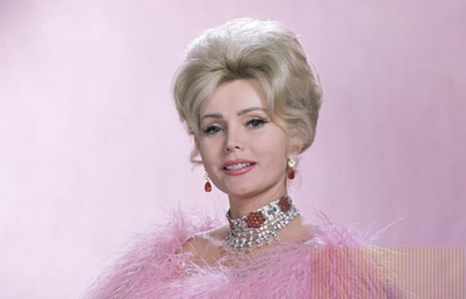 Zsa Zsa Gabor in a pink vulture feather coat and some of her jewels including a French ruby and diamond art deco wide bracelet styled as a necklace for a 1961 publicity image promoting her Dune's Club appearance in Las Vegas.