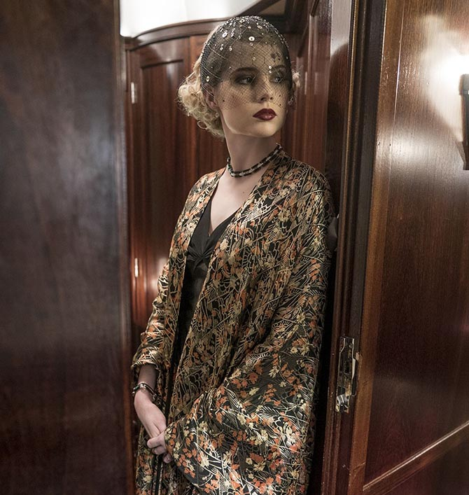 Lucy Boynton wears delicate jewels with her silk robe in 'Murder on the Orient Express.' Photo Twentieth Century Fox