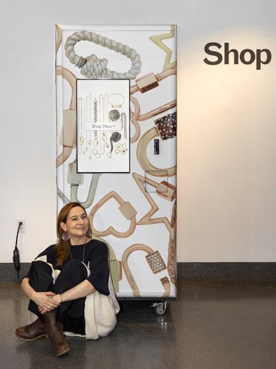 Designer Marla Aaron seated in front of her fine jewelry vending machine at the Brooklyn Museum of Art. Photo courtesy