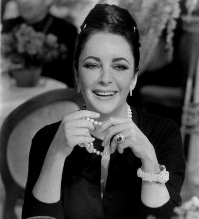 In the 1973 film 'Ash Wednesday,' Elizabeth Taylor wore her ruby and diamond Van Cleef & Arpels ring with a pearl necklace and bracelet by Daivd Webb and Cartier diamond hoop earrings. Photo Getty