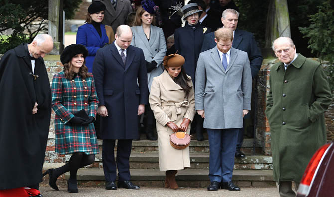 Kate Middleton, the Duchess of Cambridge and Meghan Markle curtsey while Prince William Prince Philip bow as the queen (not seen in photo) and Prince Philipp pass in front of them. Standing on the stairs are Princess Beatrice, Princess Eugenie, Princess Anne and Prince Andrew,. The royal family was attending a Christmas Day service at Church of St Mary Magdalene. Photo by Chris Jackson/Getty Images