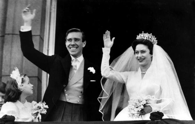Princess Margaret in the Poltimore tiara and her husband Anthony Armstrong-Jones wave to the crowd from the balcony of Buckingham Palace after their wedding. Photo Getty Images