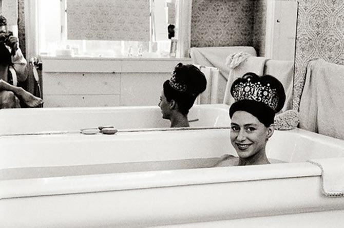 Princess Margaret wearing the Poltimore tiara in the bathtub while her husband Lord Snowdon takes a picture.