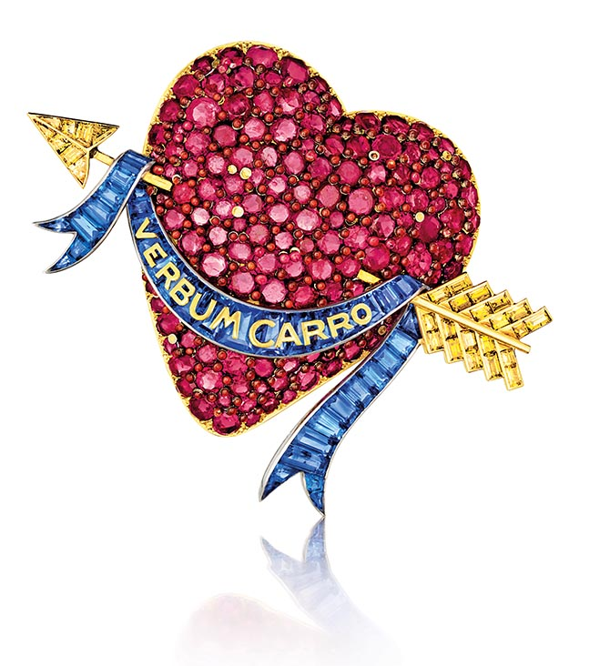 "From Ruby: Heart brooch, Verdura for Paul Flato, Rubies set in a gold heart, colored diamonds and calibré-cut sapphires in a ribbon with the phrase ""Verbum carro"" meaning ""The word made flesh"" or ""A word to my dear one."" Courtesy of Verdura"