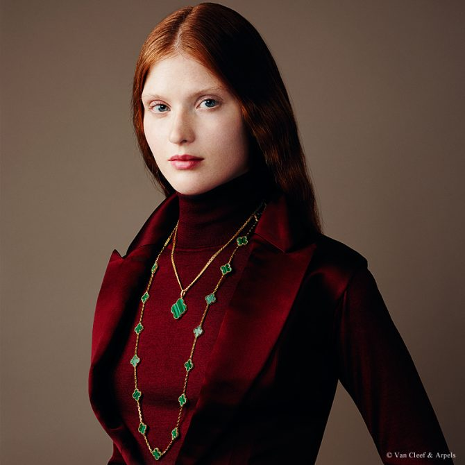 A page from a Van Cleef & Arpels catalogue of a model wearing malachite renditions of the Alhambra necklace necklace. Photo courtesy