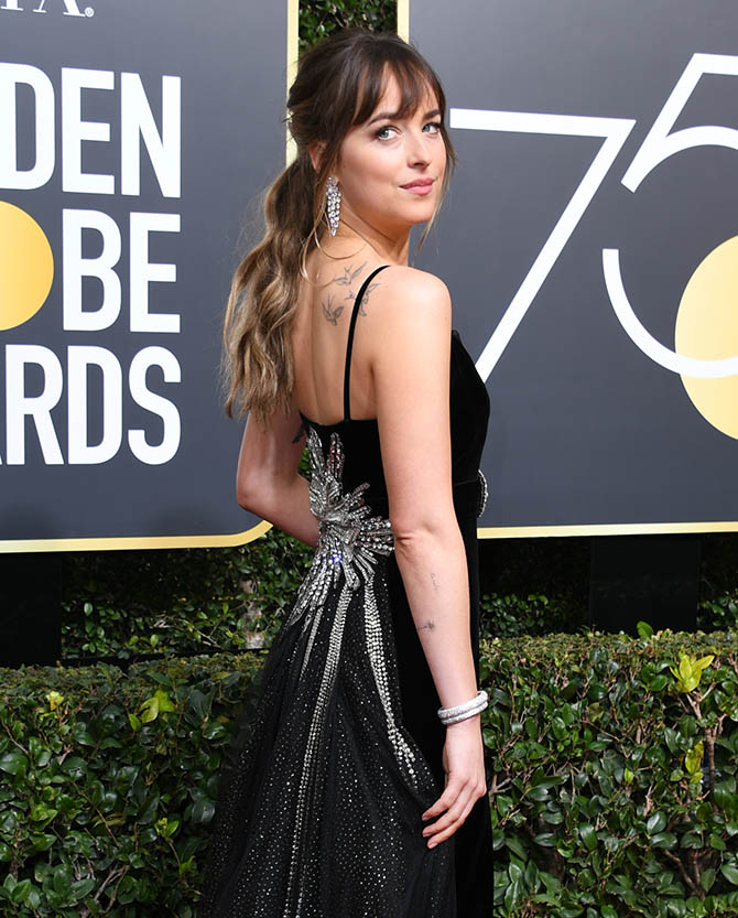 Dakota Johnson in Nirav Modi diamond earrings and bracelets and a Gucci gown at the 75th Golden Globe Awards. Photo VALERIE MACON/AFP/Getty Images