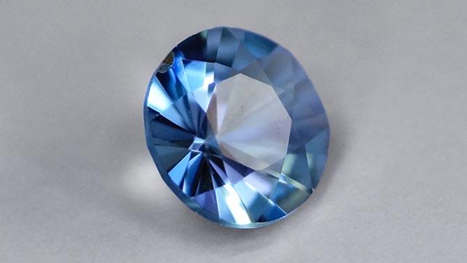 A 0.11 carat round brilliant grandidierite. Photo by Delphine Bruyère via GIA