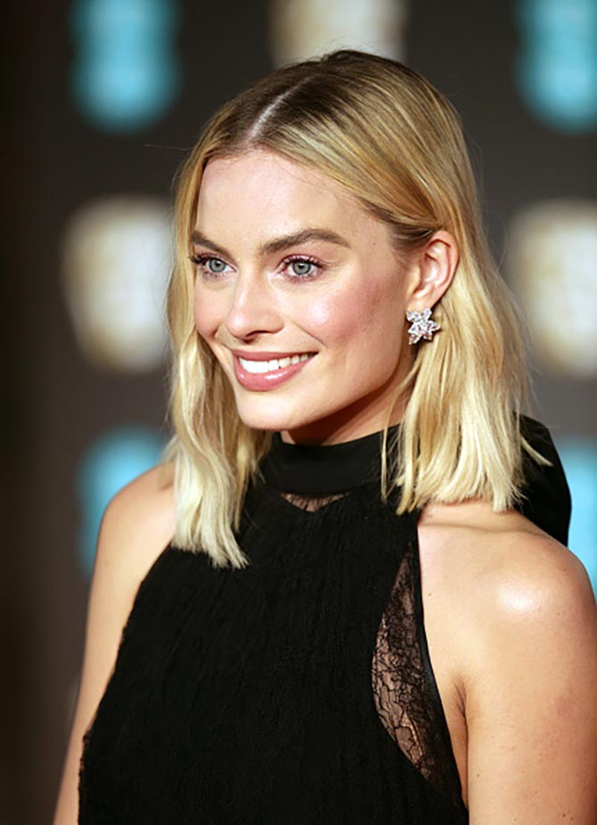 Margot Robbie in 18.75-carat diamond and platinum Harry Winston earrings.