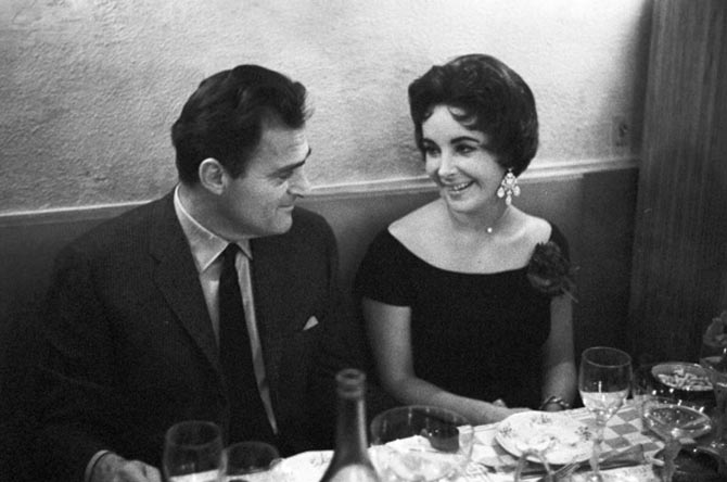 Mike Todd dining with Elizabeth Taylor in February 1958. She is wearing her diamond heart necklace and diamond chandelier earrings. Photo Getty