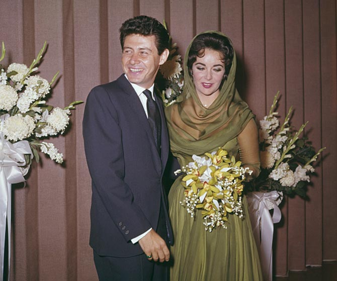 Eddie Fisher with Elizabeth Taylor who is wearing her diamond heart pendant during their wedding ceremony in Las Vegas on May 12, 1959. Photo by Rolls Press/Popperfoto/Getty Images