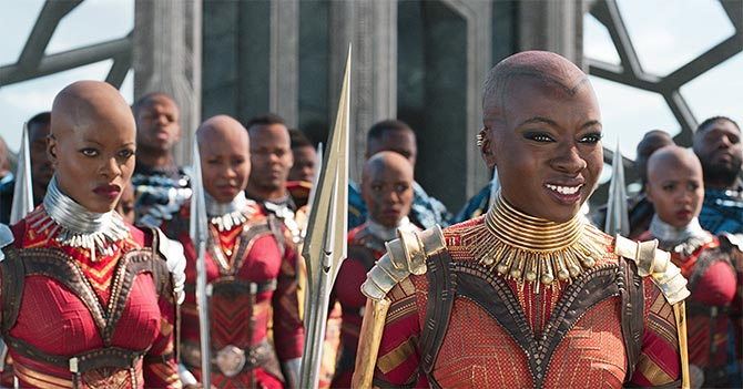 Okoye (Danai Gurira) in gold jewelry and body armor with her Dora Milaje guards who have silver jewelry and body armor. Photo Marvel Studios