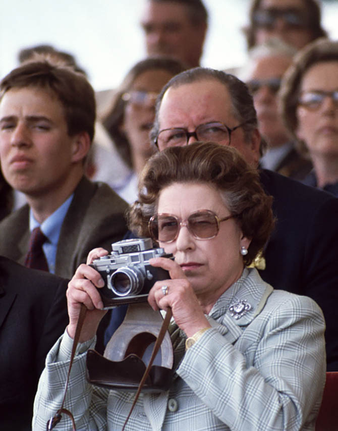 Queen Elizabeth II wearing her pearl and diamond earrings and the Cullinan V brooch as well as her engagement ring as she take photos of Prince Philip competing at the Windsor Horse Show on May 16, 1982. Photo David Levenson/Getty Images