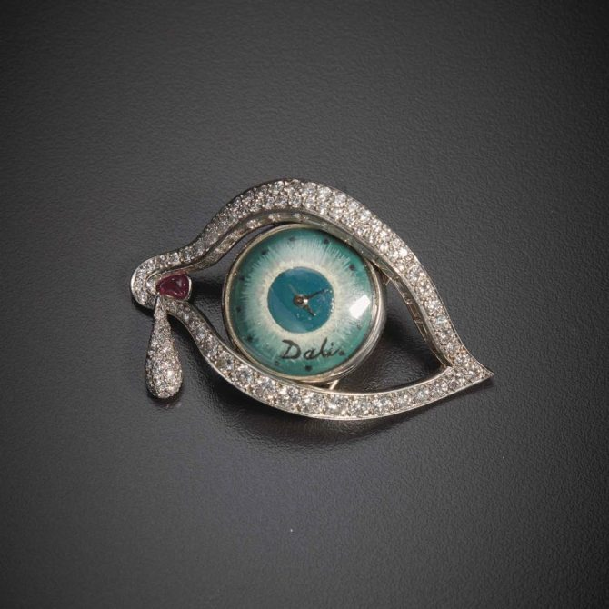 Dalí's pavé-set diamond and platinum Eye of Time brooch has baguette-cut diamonds set along the lid, a diamond tear drop pendant and a ruby at the lacrimal sac. The dial of the watch was hand painted and signed by Dalí. Movado was responsible for the mechanical movement. Photo Sotheby's