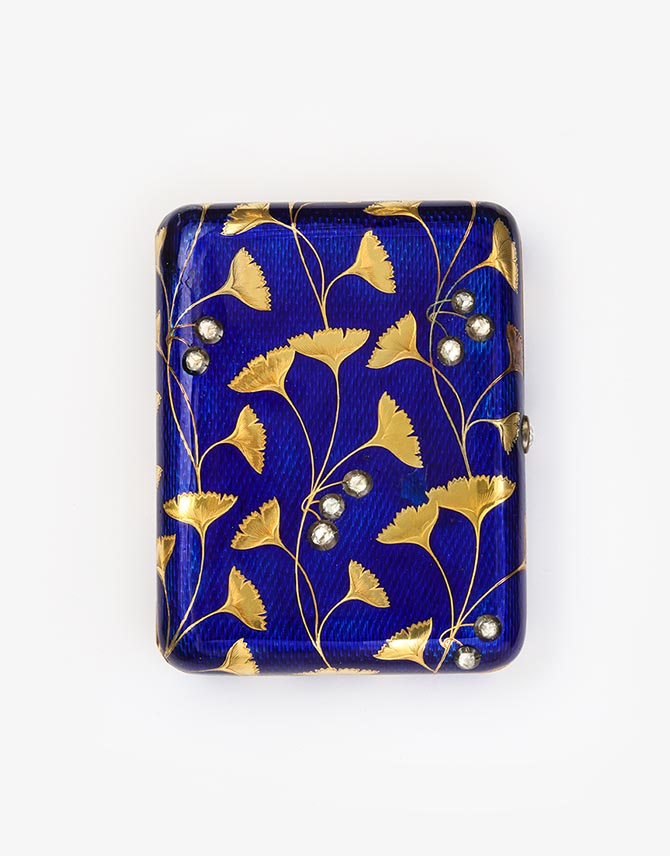 Fabergé Cigarette Case c. 1910 Gold, enamel, rose diamonds L 92 mm The Art Nouveau decoration of this gold and royal blue enamel cigarette case has an Egyptian-inspired design of gold gingko leaves with rose diamond buds.