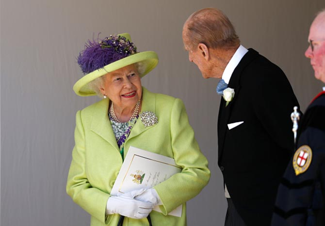 After the wedding Prince Philip, Duke of Edinburgh talking with Queen Elizabeth who is wearing a lime, lemon, purple and grey printed silk dress and coat by Stuart Parvin with a Angela Kelly hat, pearl earrings and necklace as well as The Richmond Diamond Brooch. The historic brooch was given to Princess Victoria Mary of Teck by the town of Richmond to mark her wedding to the Duke of York. The diamond and pearl jewel was made by Hunt & Roskell in 1893.