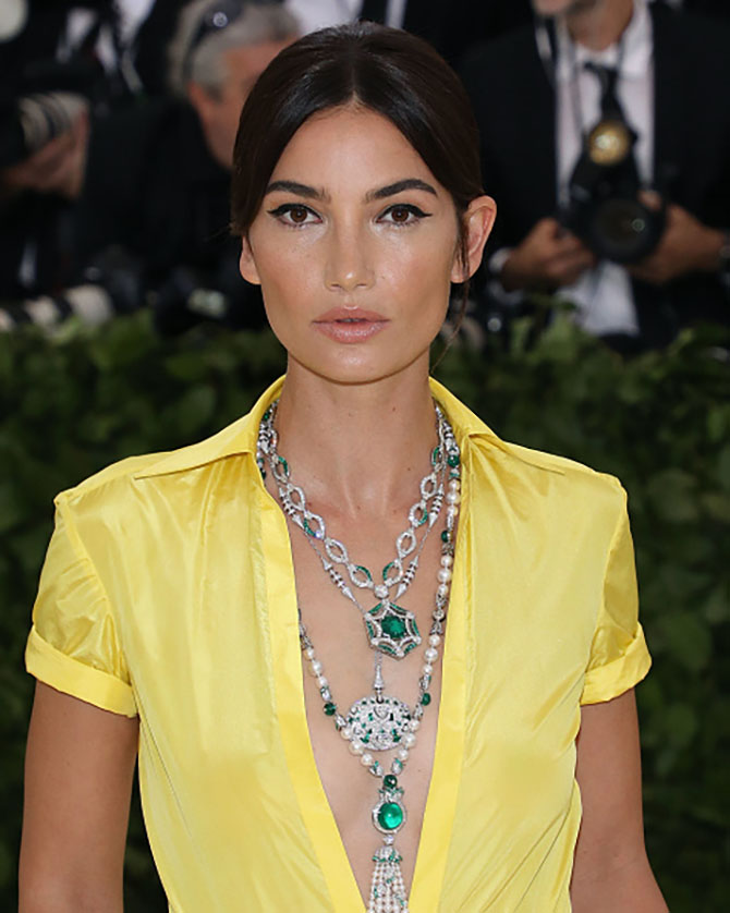 Lily Aldridge contrasted the yellow of her Ralph Lauren dress with three emerald and diamond Bulgari necklaces.