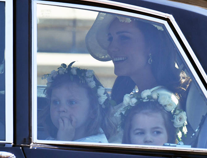 Catherine, Duchess of Cambridge arrives with Prince Harry's niece and bridesmaid Princess Charlotte, wearing primrose yellow wool silk tailored coat by Alexander McQueen, a hat by Philip Treacy and earrings from Kiki Mcdonough.