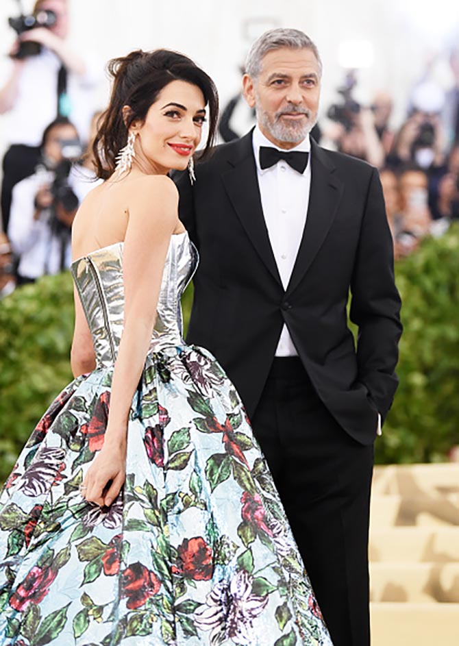 George Clooney with Amal Clooney who is wearing diamond earrings by Lorraine Schwartz and a Richard Quinn gown.