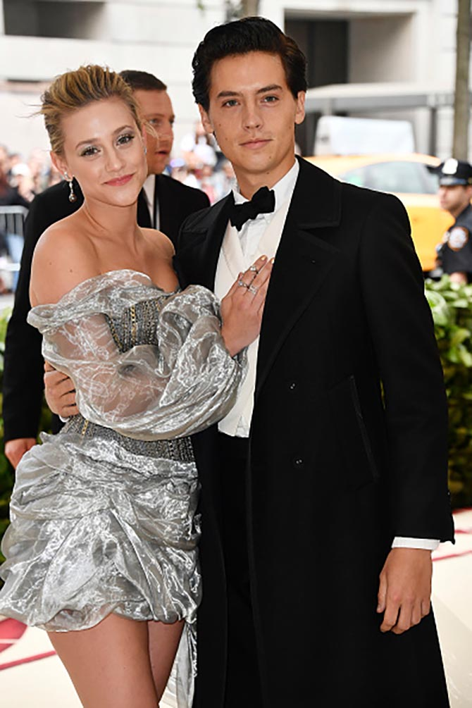 Cole Sprouse with Lili Reinhart who is wearing and H & M dress with Featherstone earrings and Djula diamond rings