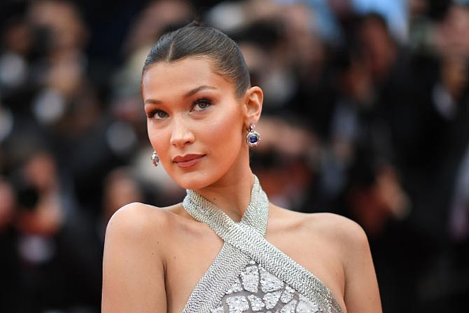 Bella Hadid paired a silver halter gown and sapphire earrings.