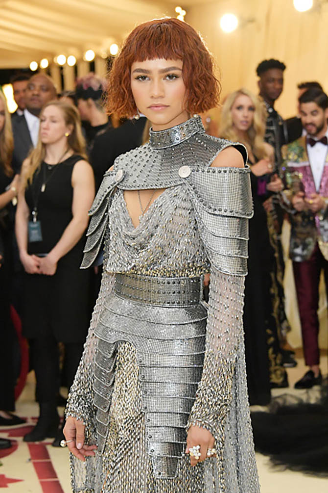 Zendaya dressed like a modern-day Joan of Arc in a chainmail-like, gunmetal colored Versace. She accessorized the dress with rings from Tiffany's newest collection Paper Flowers, a diamond ball pendant and Tiffany HardWear earrings and HardWear rings.