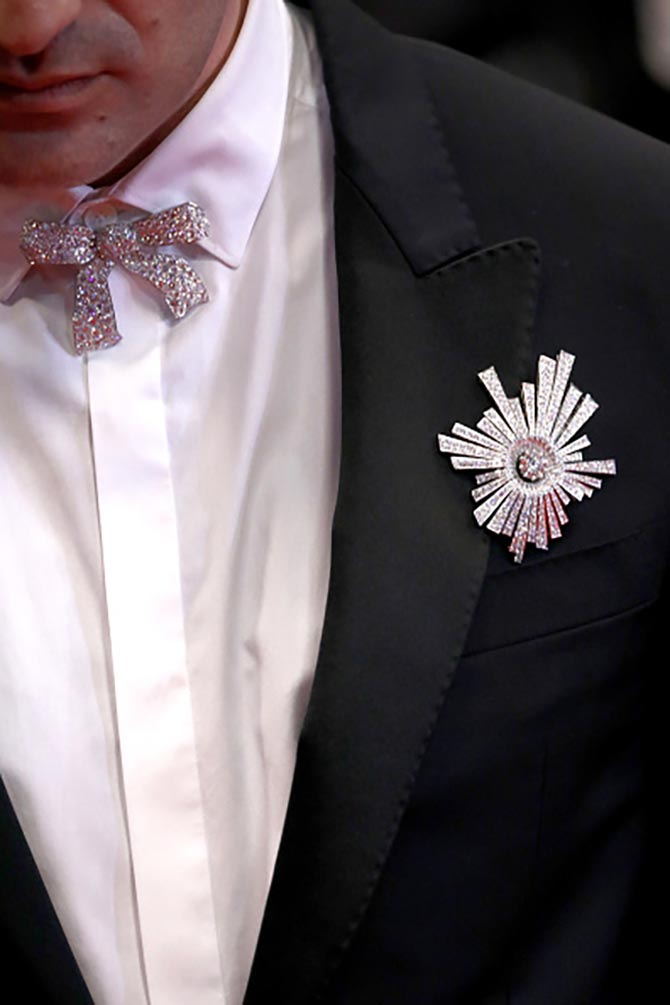 Detail of Nicolas Maury wearing two Chanel diamond brooches.