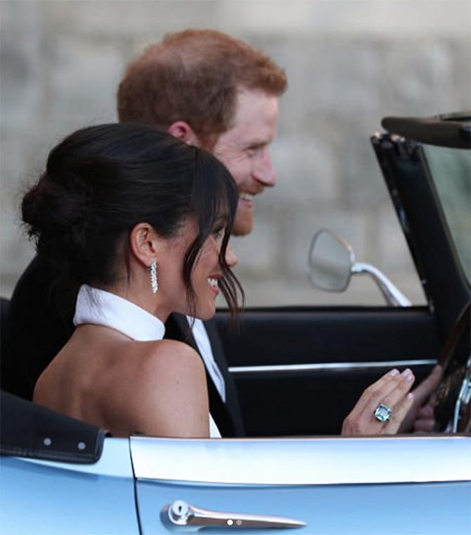 Prince Harry with Meghan Markle who is wearing Diana's aquamarine ring and her Cartier diamond earrings. Photo
