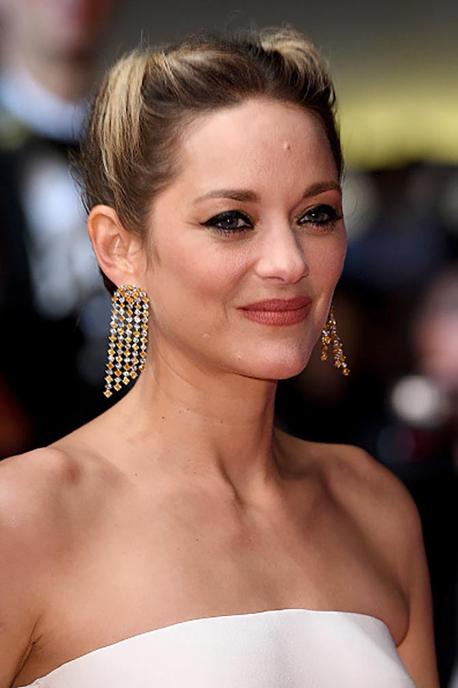 Marion Cotillard in Chopard earrings and an Armani Prive jumpsuit.