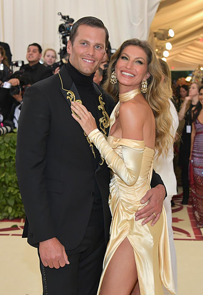 Tom Brady with Gisele Bundchen who is wearing a Versace dress and earrings by SABBA.