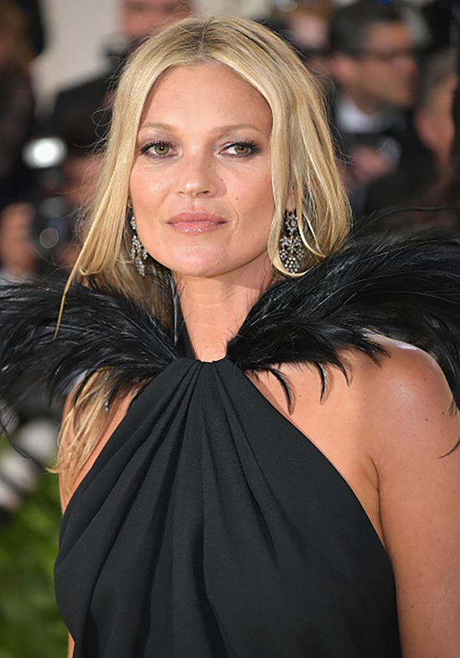 Kate Moss in vintage chandelier earrings and a Saint Laurent dress.