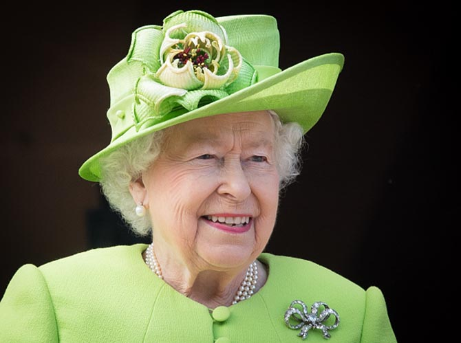 The Queen wearing her pearl and diamond studs, triple strand pearl necklace and 19th century diamond bow brooch that originally belonged to Queen Victoria. Photo Getty