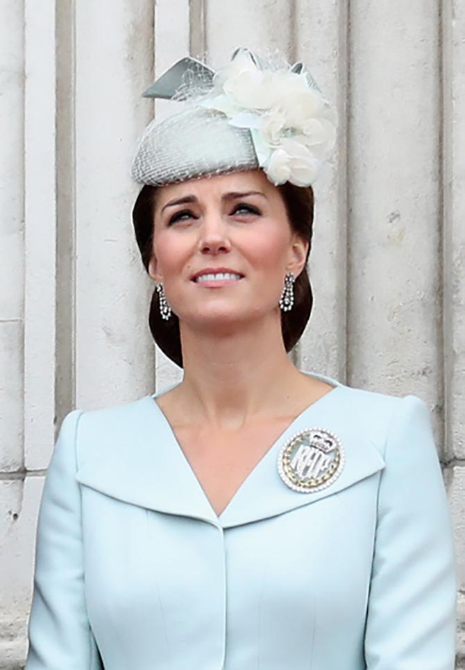 Kate Middleton, the Duchess of Cambridge, wearing antique diamond earrings, the Air Cadets Dacre brooch and an Alexander McQueen coat dress and Sean Barrett fascinator as she watches the RAF flypast at Buckingham Palace. Photo Getty