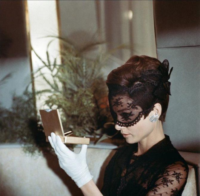 Behind the scene photo of Audrey Hepburn in 'How to Steal a Million' wearing a Givenchy ensemble with Cartier diamond earrings. She is checking her makeup in a Cartier vanity. Photo via Pinterest